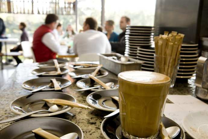 coffee at cafe with people in the background. Find out how to drink coffee like an Italian!