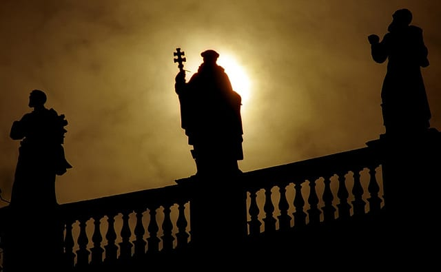 the silhouette of a saint The Piazza San Pietro, a testament to the history and power of Vatican City and its Basilica. Photo by David Ohmer