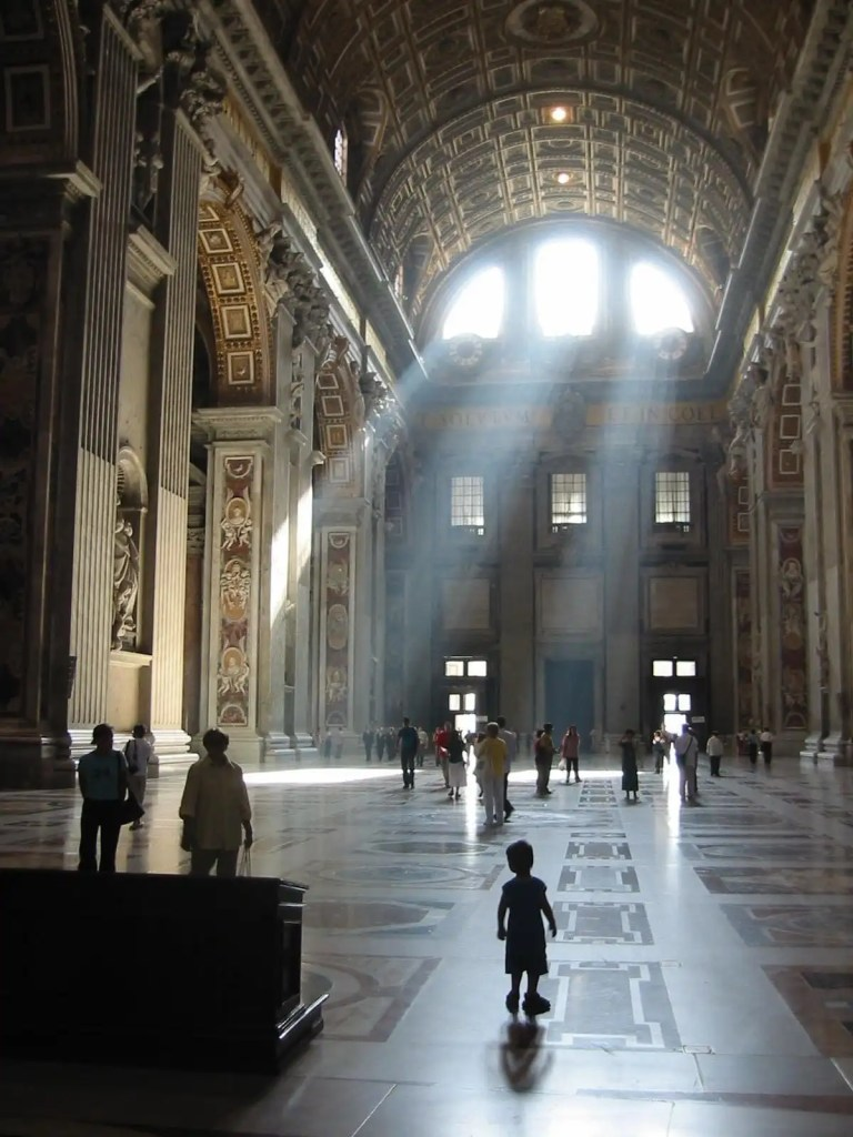 Sunlight streams through the windows, illuminating people visiting St. Peter's Basilica, Rome.