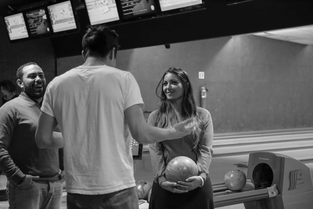 """Social Media Manager Ted Endo and self-described """"expert bowler"""" pontificates the finer points of bowling to Valeria Bove. She beat him handily, despite never having bowled in her life."""