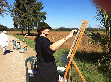 woman painting the landscape with oils during Walk the Arts art workshop and painting retreat in Italy