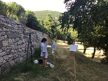 Woman in front of an easel with painting during Walk the Arts art workshops in Provence and painting holidays in France