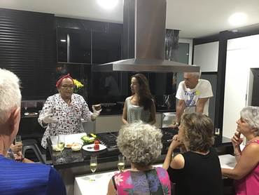 Group in a kitchen attending a cooking demonstration during Walk the Arts winter holiday in South America