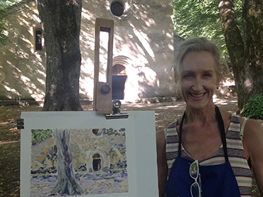 Woman artist in front of her oil painting during Walk the Arts painting workshop in Provence