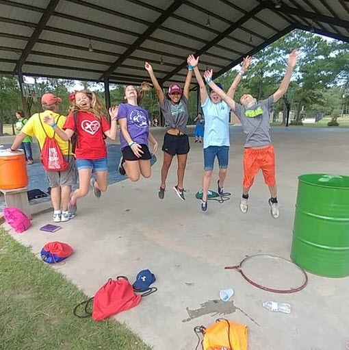 A group of adolescents jump into the air in an outdoor pavilion.