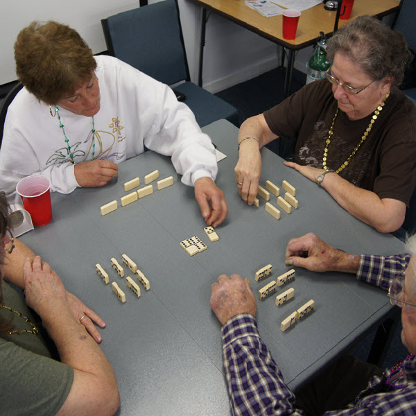 Four older adults play a game together.