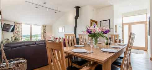 The dining area of Early Mist cottage with table and chairs where families ca get together and enjoy the woodburner
