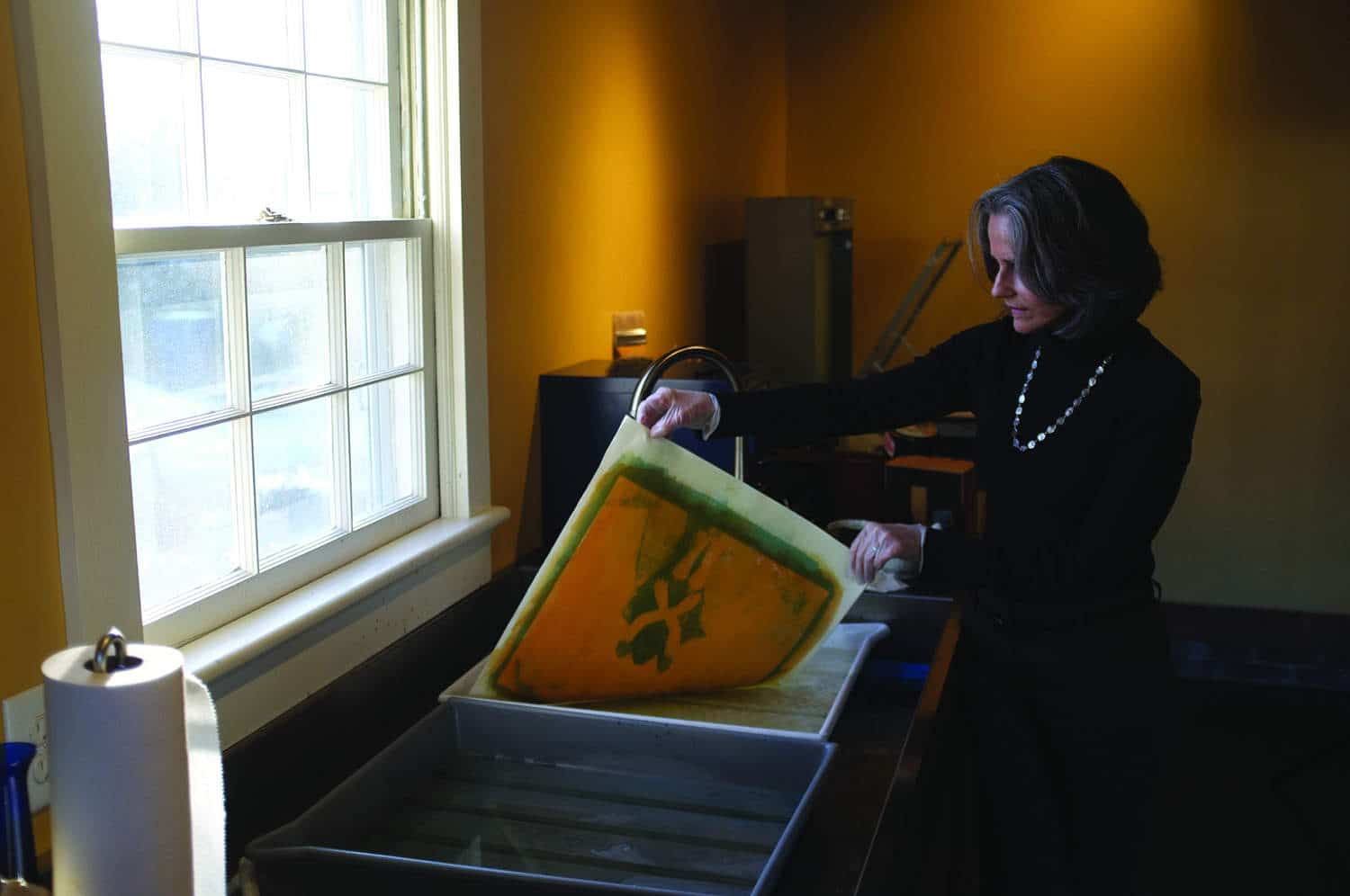 Diana Bloomfield rinsing a gum print in her Raleigh studio.