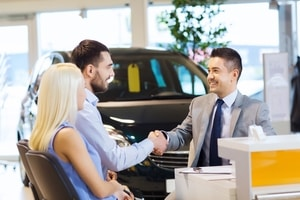 auto business, car sale, and people concept - happy couple with dealer shaking hands in auto show or