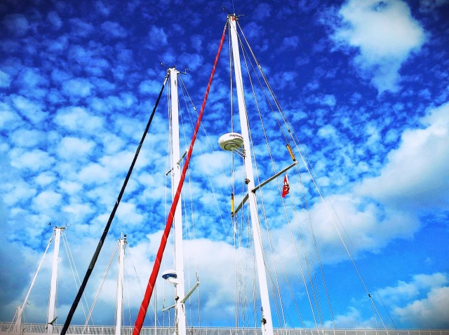 Sailboat masts against a blue sky with clouds