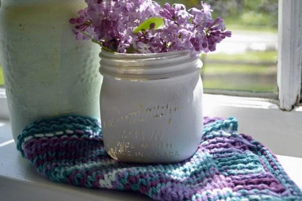 Vintage white chalk painted mason jar with purple lilac followers sitting on a window sill on the framed zig zag knit dishcloth pattern cloth