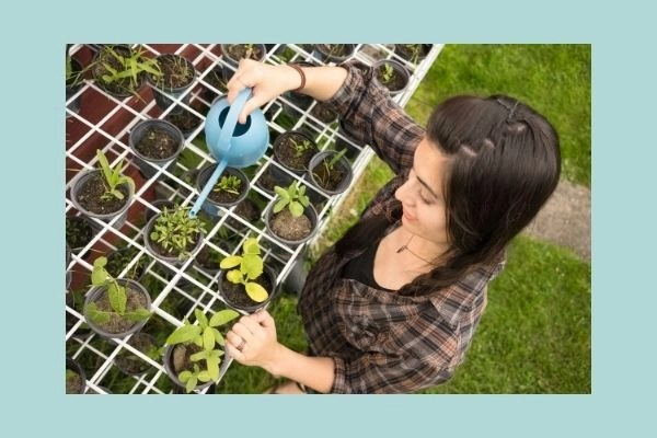 girl watering her plants outdoors with a blue watering can and a happy smile on her face