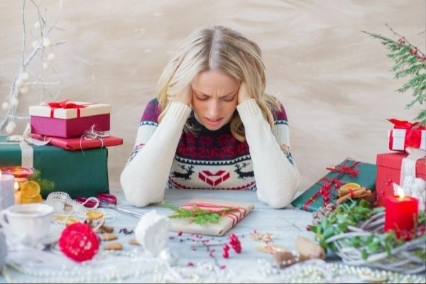 mom with christmas sweater on, sitting at table with christmas gifts and hands on head showing she's stressed.