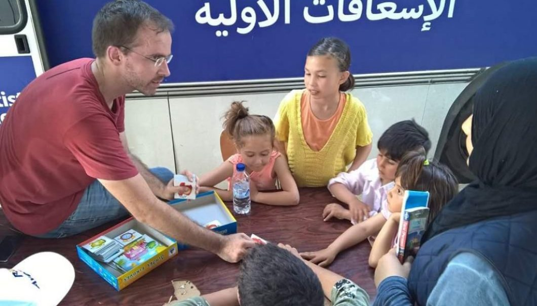 """Friederich, an amazing S. African doctor we had the privilege of working with playing """"Memory"""" with the kids and using it as an opportunity to teach English."""