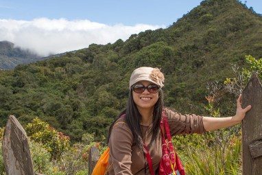 A woman wearing hat and sunglasses takes a break near the top of a jungle mountain - Legend of El Dorado in Colombia