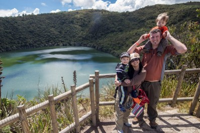 A young family smiles while standing on an over look over a crater lake surrounded by jungle - Legend of El Dorado in Colombia