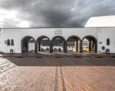Storm clouds roll over a white building with arched doorways - Legend of El Dorado in Colombia