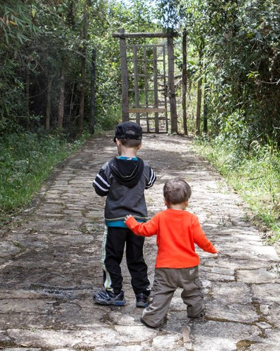 Two young brothers walk together up a path towards a gate searching for the Lost City of Gold in Guatavita Colombia with Kids
