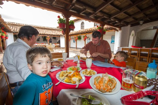 A young family eats lunch in an open air spanish style building - Legend of El Dorado in Colombia