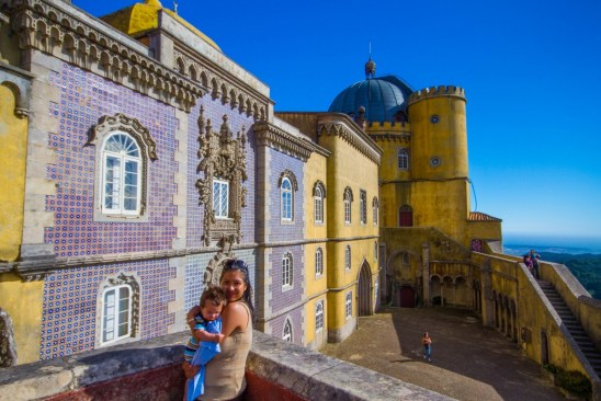 A woman and baby pose in front of the colourful facades of the Pena Palace in Sintra, Portugal