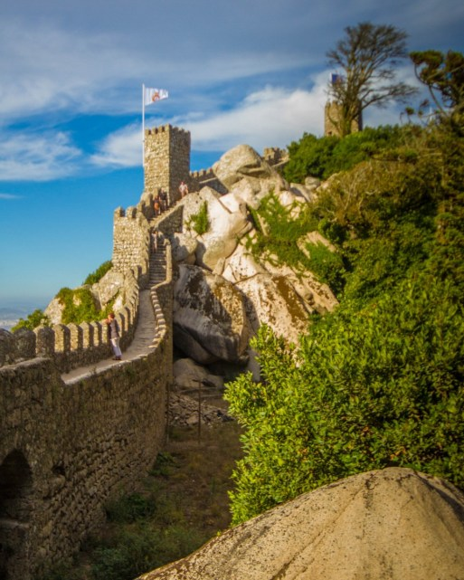A castle rampart lined with flags on a mountain ledge with a forest on the inside - Sintra, Portugal