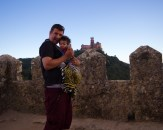 Father holds his son in a Baby Bjorn in front of Sintra Castle in Portugal - helping kids find nap time on the road