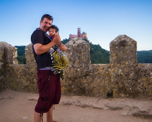 Man wearing shorts holds a little baby while on a castle wall - Sintra, Portugal