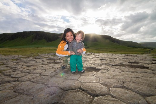 mother and young boy smile while standing on basalt rocks