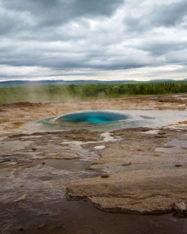 A blue bubble of water rises from the ground as a geysir is about to erupt - Iceland's Golden Circle