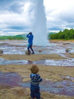 A child watches from a distance as a man holds on to his hat when a geysir erupts next to him - Iceland's Golden Circle