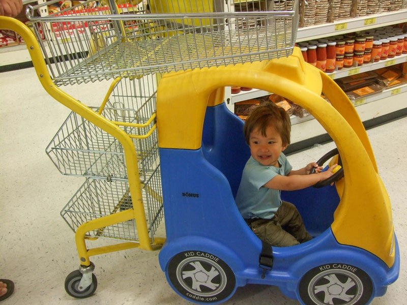 boy sits inside a race car grocery cart in Iceland for kids