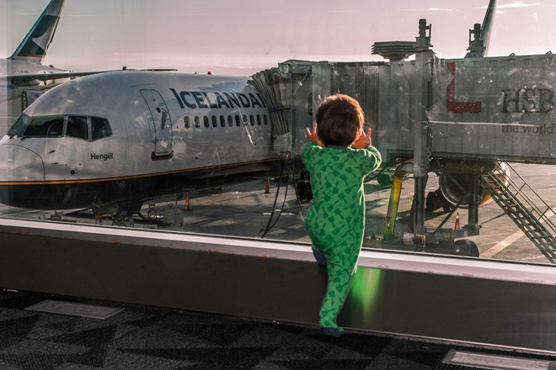 A toddler in pajamas looking out the window of an airport at an Icelandair plane at sunset as they prepare to travel Iceland's Golden Circle with kids