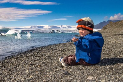 A young boy sits near an iceberg filled lagoon