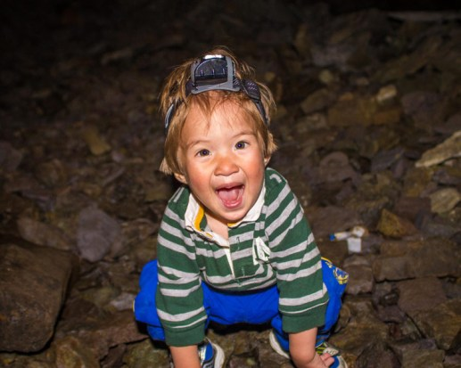 young boy smiles while wearing a headlamp in a cave