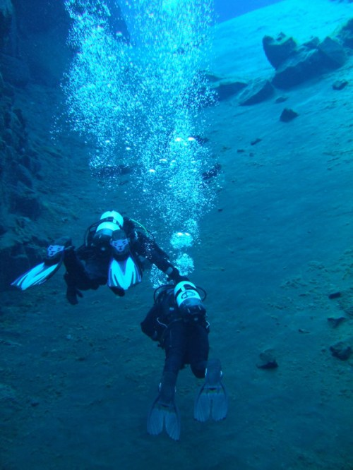 SCUBA divers in crystal clear waters surrounded by bubbles - Diving Iceland's Silfra