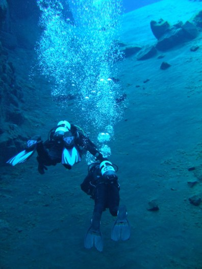 Two SCUBA divers exhale bubbles in some of the clearest waters in the world at the Silfra Iceland in Thingvellir National Park
