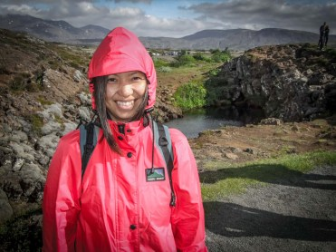 An asian worman wearing a raincoat smiles with a rocky and beautiful background - Diving Iceland's Silfra