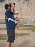 Man takes photographs in Mexio while carrying an infant in a Baby Bjorn - helping kids find nap time on the road