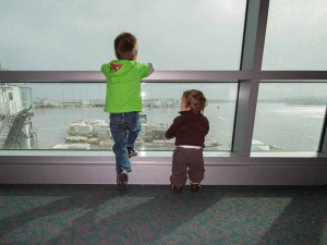 Two boys staring out the window of an airport