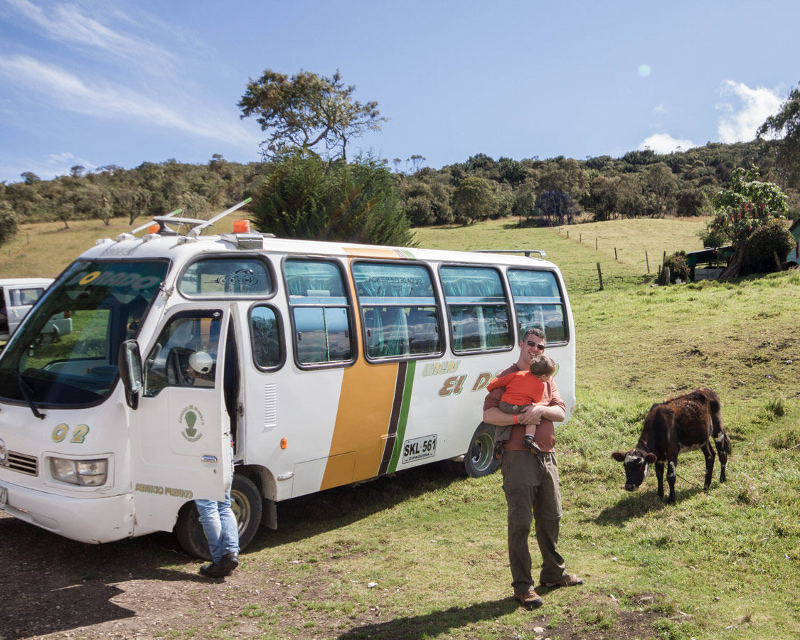 A father standing near a bus shows his baby a young cow after searching for the lost city of gold in Guatavita Colombia with kids