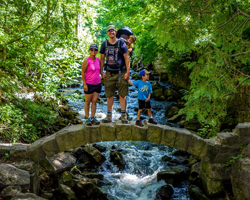 A smiling family stands on an old stone bridge over a stream - Limehouse Conservation Area