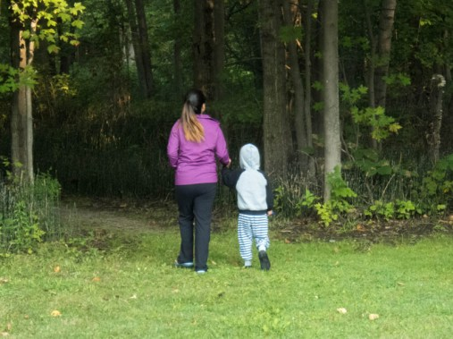 A woman and a young boy walk towards the woods in a forest while camping in Mara Provincial Park
