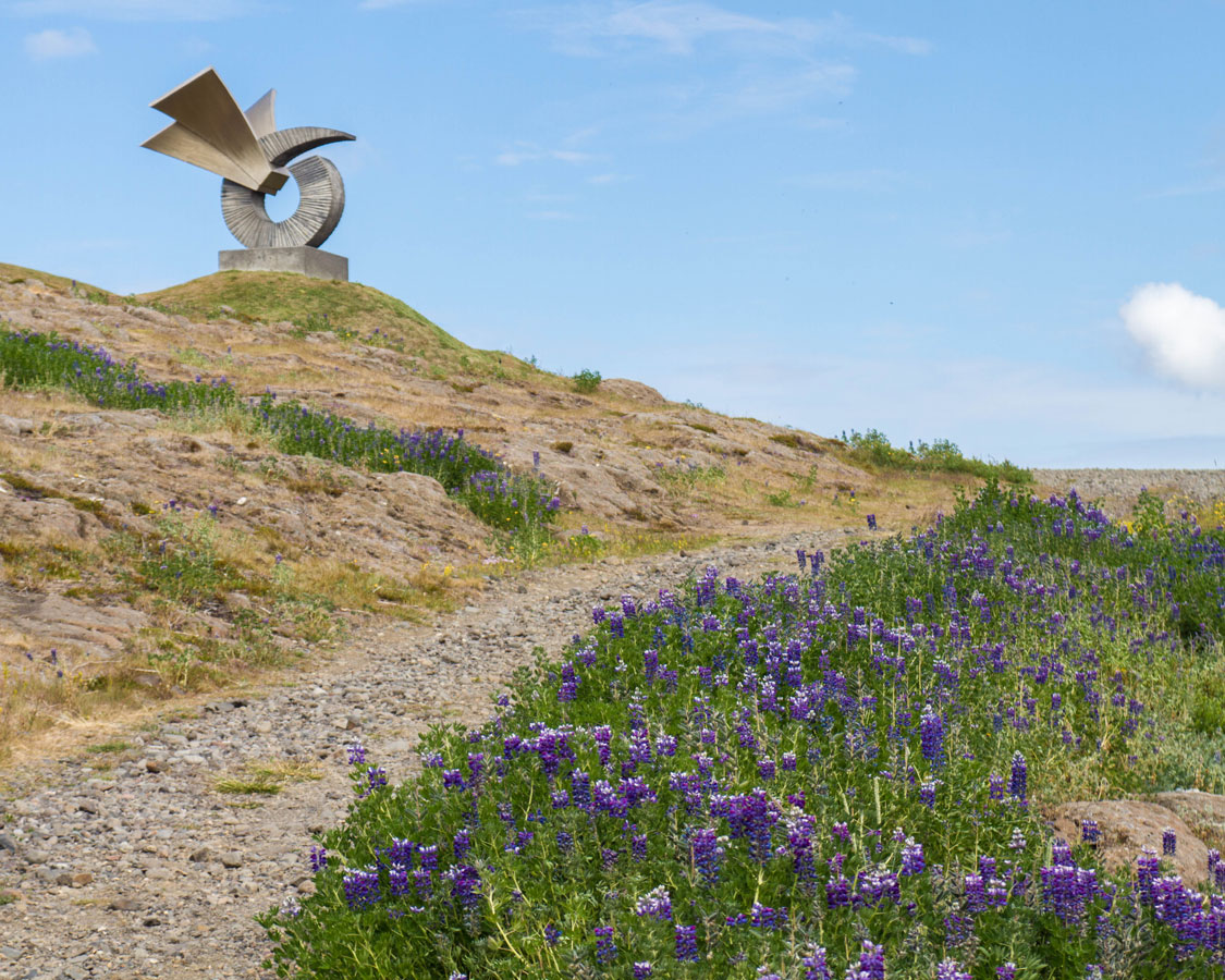 A statue sits on a rock face in in Thingvellir National Park in Iceland near a hiking path with wildflowers growing along it