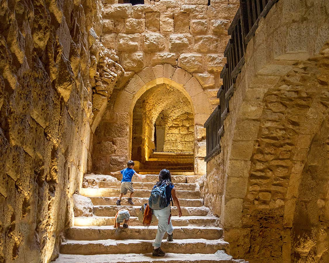 Climbing the stairs of Aljoun Castle in Jordan