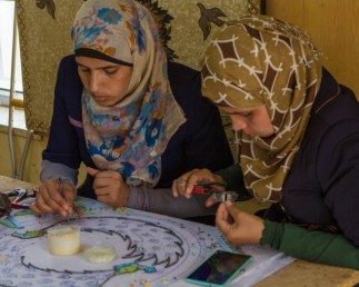 Two Arabic women in head scarfs creating tile art