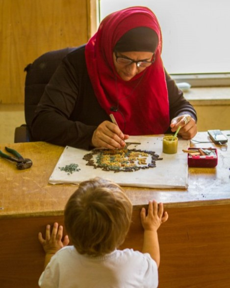 Young boy watches an Arabic woman create a mosaic artwork