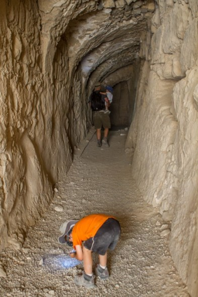Young boy searches the ground for treasure in a tunnel - Traveling Jordan with Kids