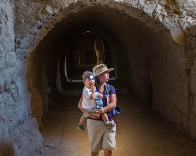 Woman and toddler wearing headlamp exploring castle tunnels