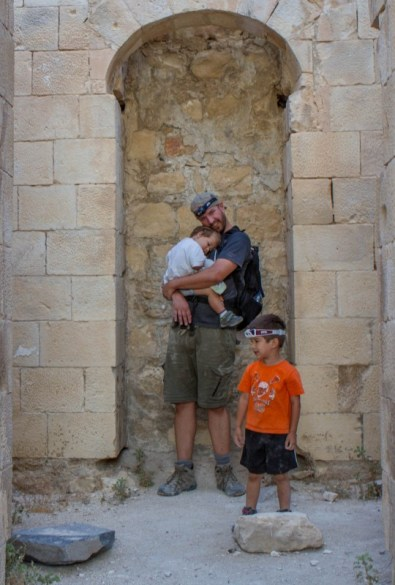 Father snuggles a toddler while a young boy watches in an ancient castle