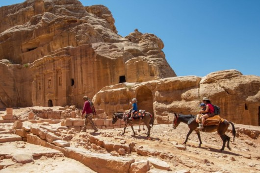 Family rides horses through Petra